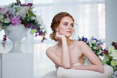 Portrait of a beautiful girl in a wedding dress. Bride in luxurious dress sitting on a chair. Portrait of a beautiful girl in a wedding dress. Bride in a royalty free stock photos