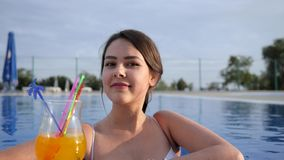 Portrait of Beautiful girl which drinking colorful cocktail pool on open air in Summer holiday. Portrait of Beautiful girl which drinking colorful cocktail in stock video footage