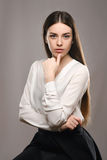 Portrait beautiful girl in white blouse and black skirt. Beauty portrait young girl sitting at the white table in white blouse and black skirt on gray background Stock Photography