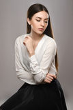 Portrait beautiful girl in white blouse and black skirt. Beauty portrait young girl sitting at the white table in white blouse and black skirt on gray background Royalty Free Stock Photos
