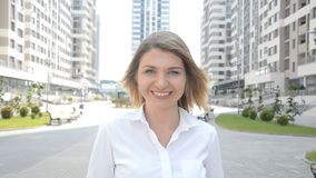 Portrait of a beautiful girl in a white blouse who looks into the camera and smiles. Against the background of a modern residential complex stock video