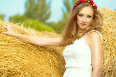 Portrait of beautiful girl in white sundress standing among haystacks at the countryside with garland made of artificial fruits on Royalty Free Stock Image