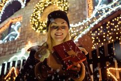 Portrait of a beautiful girl who opens a magic Christmas gift in. Front of house decorated with Christmas lights. Christmas, holidays, winter and people concept Royalty Free Stock Photos
