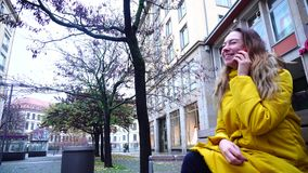 Portrait of beautiful girl who speaks by mobile sitting on bench in city on background of houses on cool autumn day. Good-looking female chatters on cell and stock video footage