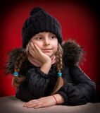 Portrait of beautiful girl in winter cloth. On a red background Royalty Free Stock Photos