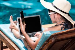 Portrait Beautiful girl woman enjoying relaxing with mobile phone near swimming pool. Blue water royalty free stock image