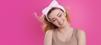 Portrait of a beautiful girl woman in a headband for make up on pink studio background, concept of beauty, advertising cosmetics, stock images