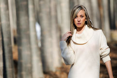Portrait of a beautiful girl in the woods. Beautiful blonde girl, dressed with a beige dress, standing in a poplar forest Stock Photography