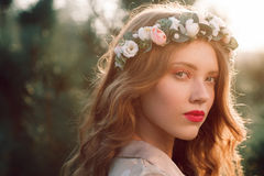 Portrait of beautiful girl in wreath at sunset Stock Photo