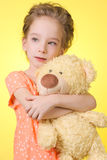 Portrait of beautiful girl 6 years which hugs a Teddy bear - isolated on yellow background Royalty Free Stock Images