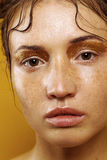 Portrait of a beautiful girl on a yellow background with the effect of wet skin. The girl with freckles on a yellow background Stock Photo