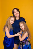 Portrait of beautiful girls in blue dresses on a yellow background in the studio royalty free stock image