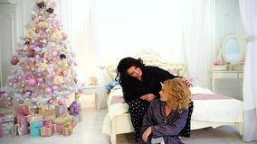 Portrait of beautiful girls. Elder sister cares about appearance of younger, being in bright bedroom with festive. Brunette woman adjusts neatly hair to blonde stock footage