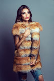 Portrait of a beautiful glam model in fox jacket. Portrait of a beautiful glam model with provocative make up and long shining hair wearing fox jacket.  Natural Stock Photos