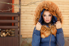 Portrait of a beautiful glamorous girl in a fur hat and a red co Stock Image