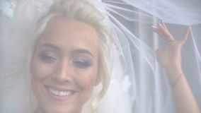 Portrait of the beautiful gorgeous blonde bride with charming smile posing under veil. stock video footage