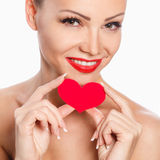 Portrait of Beautiful gorgeous smiling woman with glamour bright makeup and red heart in hand Royalty Free Stock Photo