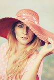 Portrait of a beautiful graceful woman in elegant pink hat with a wide brim. Beauty, fashion concept. Looking in the Stock Images