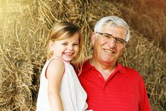 Little girl with grandpa on the farm. stock photo
