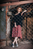 Portrait of beautiful grunge girl in plaid skirt and sweater standing behind metallic lattice Stock Image