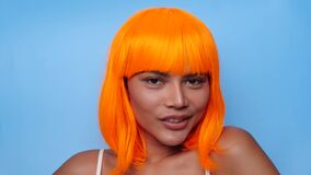 Portrait of beautiful happy Asian woman in bright orange wig posing over blue