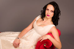 Portrait of a beautiful happy bride on red sofa Royalty Free Stock Photo