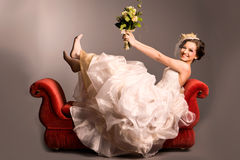 Portrait of a beautiful happy bride on red sofa Stock Images