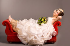 Portrait of a beautiful happy bride on red sofa Stock Photos