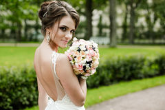Portrait of a beautiful happy brunette bride in wedding white dress holding hands in bouquet of flowers outdoors Royalty Free Stock Images