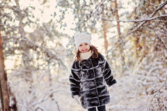 Portrait of beautiful happy child girl walking in winter sunny forest Stock Photo