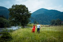 Portrait of the beautiful happy couple holding hands and walking along daisy meadow near the river in the mountains. Covered with green trees Stock Image