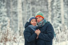 Portrait of a beautiful happy couples in winter forest. Husband and wife smiling. stock photos