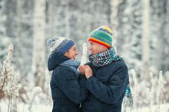 Portrait of a beautiful happy couples in winter forest. Husband and wife smiling. Stock Image