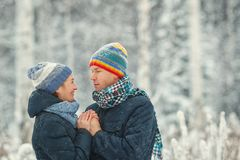 Portrait of a beautiful happy couples in winter forest. Husband and wife smiling. stock photo