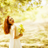 Portrait of beautiful happy ginger girl with yellow leaves in th stock image