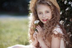 Young lady in a straw hat on a spring lawn among flowering bushes Stock Images