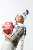 Portrait of beautiful happy girl in sweater hat and mittens with box of Christmas gift on a white background Stock Photo