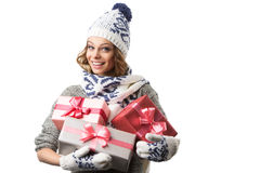 Portrait of beautiful happy girl in sweater hat and mittens with boxes of Christmas gifts Royalty Free Stock Images
