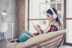 Portrait of beautiful happy latin girl sitting in stylish armchair at home with phone and listen to music with white royalty free stock images
