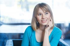 Portrait of beautiful happy satisfied blonde young woman in blue t-shirt with makeup and bangs hair sitting, touching her face and. Looking aside and dreaming stock photos