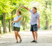 Portrait of a beautiful happy senior couple in love dancing in the park. Happy smiling senior couple in love, dancing and having fun in the park. Being together Stock Image