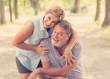 Portrait of a beautiful happy senior couple in love relaxing in the park. Happy smiling senior couple in love, relaxing, dancing and having fun in the park Royalty Free Stock Photos
