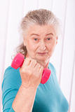 Happy senior woman with dumbbells Stock Photo
