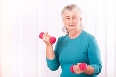 Happy senior woman with dumbbells Royalty Free Stock Images