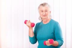 Happy senior woman with dumbbells. Portrait beautiful happy senior woman with dumbbells Royalty Free Stock Images