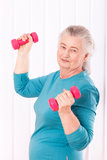 Happy senior woman with dumbbells Stock Images