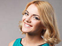Portrait of the beautiful happy smiling girl posing in studio. Stock Photos