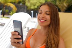 Portrait of beautiful happy smiling woman using samart phone while lying on deck chair on beach. Girl on summer holidays vacation. Mobile communication stock photos