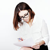 Portrait of beautiful happy smiling young office woman working with paper at office desk Royalty Free Stock Photography