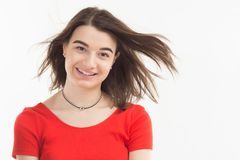 Portrait of a beautiful happy smiling young woman wearing red t-shirt wind blows her hair, background, studio shoot.  Royalty Free Stock Photography